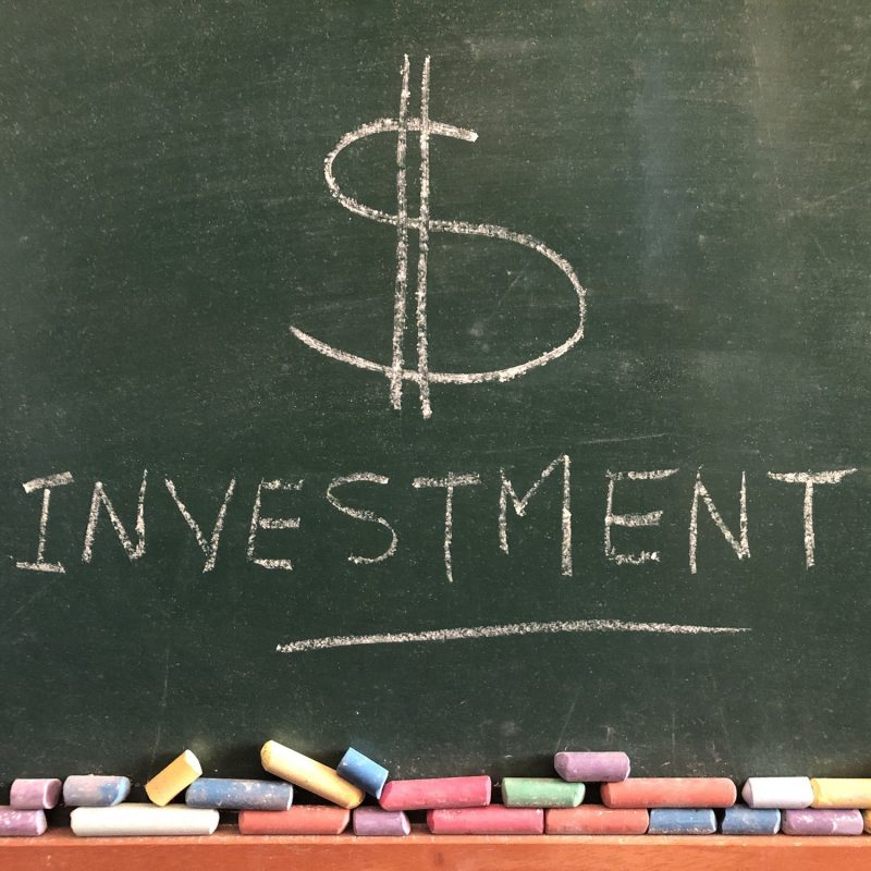 $ Investment, written in chalk on a chalkboard. Creative concept, banking and finance